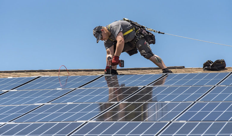 Wyatt Whelan, PosiGen install supervisor, secures a photovoltaic panel to a roof May 11, 2018, at Dover Air Force Base, Del. One hundred forty-nine houses in the Dover Family Housing community are scheduled to have the panels installed on them. (U.S. Air Force photo by Roland Balik)