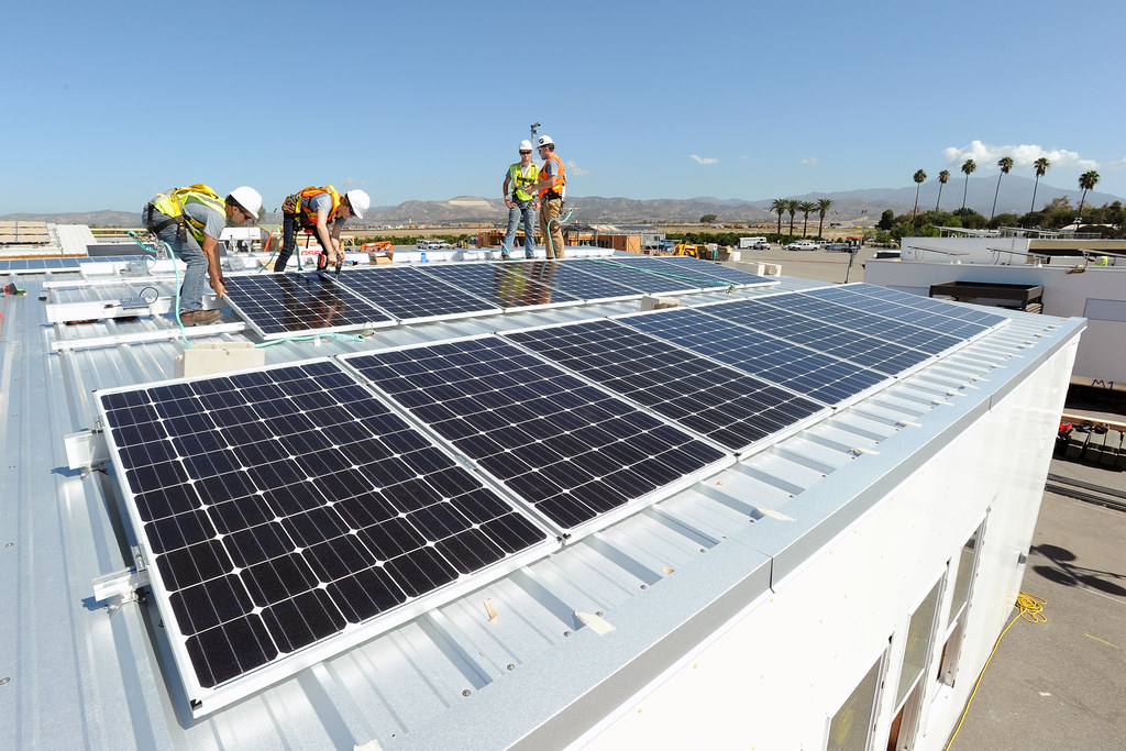 Clemson University team members Neely Leslie (left) and Justin Hamrick install  solar panels under the sun on Day 5 of the U.S. Department of Energy Solar Decathlon at the Orange County Great Park, Irvine, California Friday, Oct. 2, 2015. (Credit: Thomas Kelsey/U.S. Department of Energy Solar Decathlon)